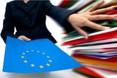 Femme repoussant une pile de documents pour laisser la place à un dossier aux couleurs de l'UE © CE