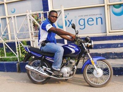 Un des 30 motards en tenue de travail avant leur tournée journalière devant le siege social d'Oxigen Rdc... Image d'Oxigen (c.)