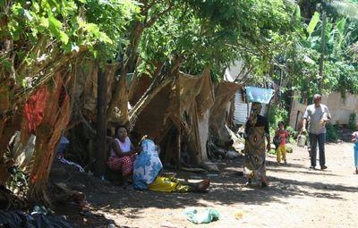 Scène de vie dans le quartier Doujani 1 Collège : une femme avec une bassine sur la tête passe devant d'autres habitantes assises devant leur bicoque (maison précaire) (c) Emmanuel Tusevo Diasamvu