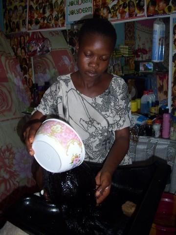 Une employée de Jolyderm en train de faire un shampoing (c) R. A. Dide