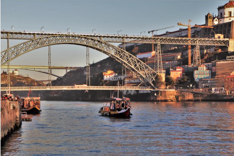 Un bateau traditionnel navigue sur le Douro, à Porto. Il s'apprête à passer sous le plus célèbre pont de la ville, le Ponte Luis 1, dominé par le Claustros do Mosteiro da Serra do Pilar (en haut à droite). / © E.V.