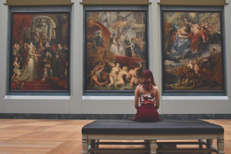 Une femme assise au musée du Louvre contemplant une triptyque, nous fait poser la question de notre propre consommation de biens culturels pendant cette période de confinement. (c)Pixabay