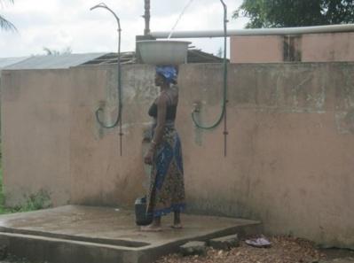 Prise d'eau par une femme du village sur la tête de forage aménagée. Photo (c) Alain Tossounon
