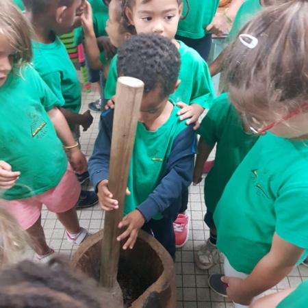 """Les enfants écrasent eux-mêmes les graines."""" (c) École Beraca."""