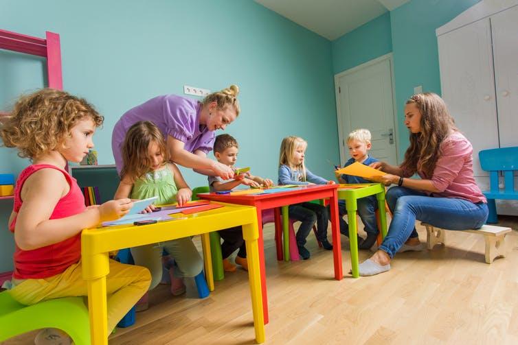 Les femmes de service accèdent à des tâches éducatives au fur et à mesure que l'école maternelle et le métier d'enseignant·e en maternelle évoluent. Shutterstock