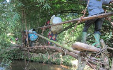 Suite à l'insécurité, des civils quittent leurs villages et traversent une rivière sur un pont traditionnel. Photo (c) Pierre Buingo, Sud-Kivu, décembre 2014