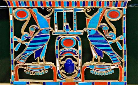 Détail d'un pendentif reprenant les motifs sacrés: Khéper au centre entouré de deux représentations d'or perché sur le signe Nébou. Photo (c) Charlotte Service-Longépé
