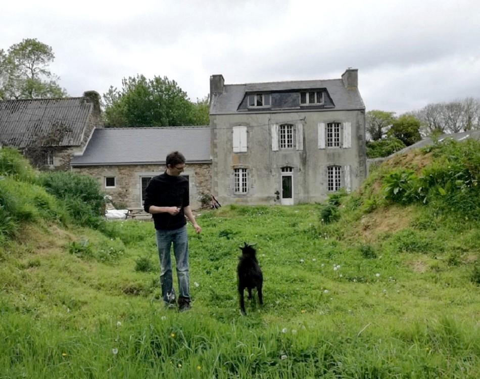Olivier jouant avec Boutok devant le corps de ferme attenant à la chapelle de Loc Maria (c) E.V.