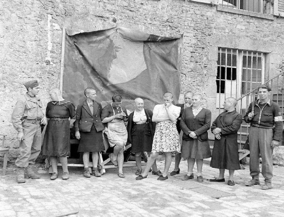 Un groupe de huit femmes tondues sous la surveillance de deux FFI. La scène se déroule au camp dépendant de Vichy, dans la Manche (c) Flickr