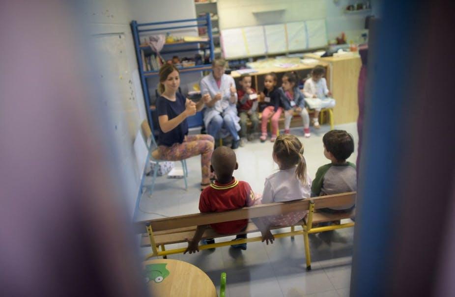 Une enseignante et une ATSEM accueillent une classe lors de la rentrée à l'école maternelle Merlin, en 2015. Lionel Bonaventure/AFP