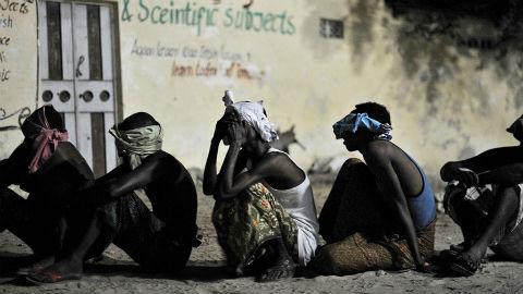 A Mogadiscio, des militants présumés d'al-Shabaab attendent d'être emmenés pour être interrogés au cours d'une opération conjointe par les services de sécurité somaliens et la Mission de l'Union africaine en Somalie (AMISOM). Photo (c) ONU / Tobin Jones