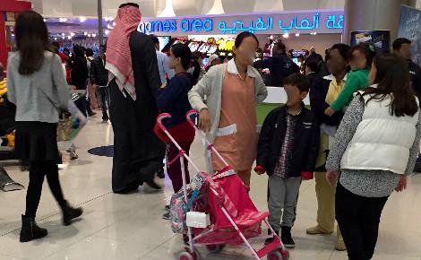 """Aire de jeux du centre commercial """"Avenues"""" où deux travailleuses domestiques s'occupent de trois enfants dont les parents font du shopping. Photo (c) Bulent Inan."""