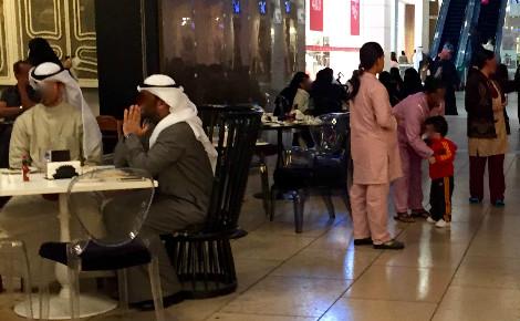 Trois travailleuses domestiques, repérables à leur uniforme, s'occupent de l'enfant dont les parents dînent au restaurant. Photo (c) Bulent Inan.