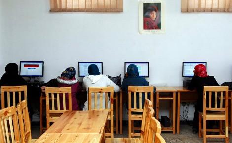 """Lycéennes afghanes en salle informatique où figure """"La femme afghane"""" qui incarne la souffrance et la dignité (cliché pris en 1984 par Steve McCurry). Image du domaine public."""