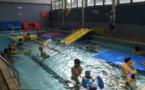 Les bébés nageurs surfent sur la vague